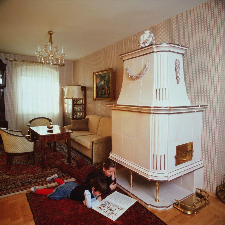 Wohnzimmer Kachelofen mit geschwungenen aufsatz und bekrönung in weiß