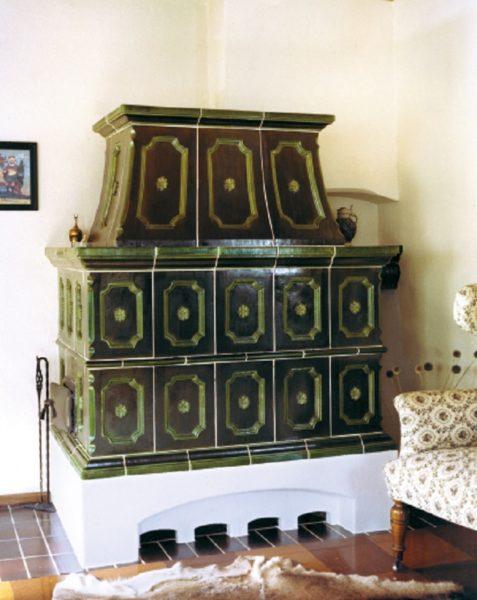 grüner imposanter Grundofen mit gemauerten Sockel
