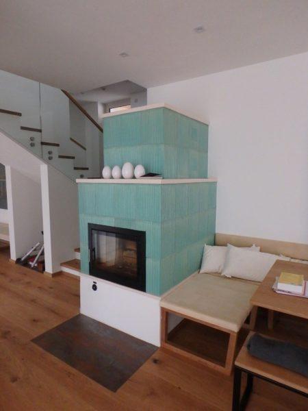 mintgrüner Kachelofen modern mit sichtfenster