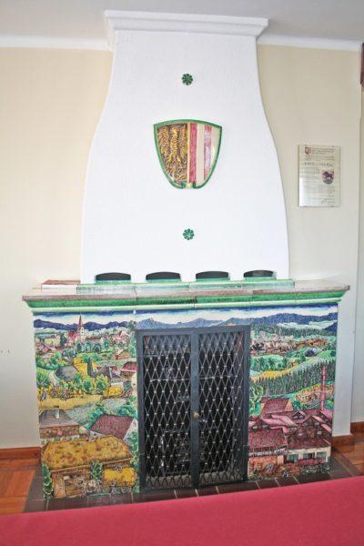 Kachelkamin mit großflächiger bunter Landschaftsmalerei