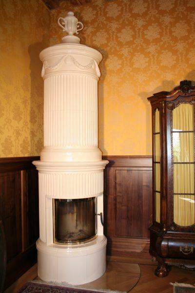 eleganter runder Kachelofen mit großem Sichtfenster, Kanelurenofen